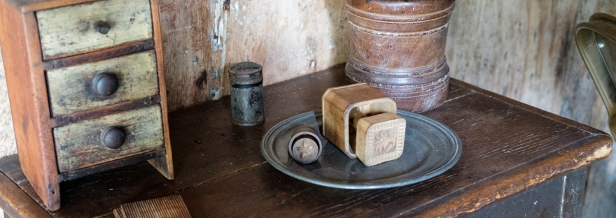 Photograph of reproduction pewter plate, comb, mug, and small box with drawers on wooden table