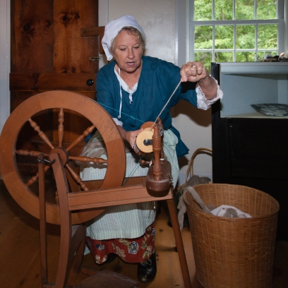 Female reenact sewing at spindle wheel