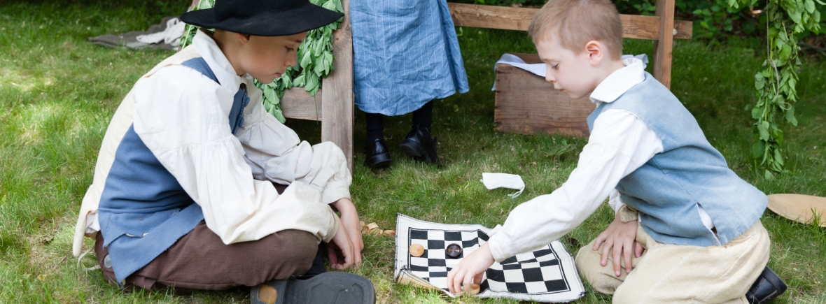 Photograph of children dressed in 17th century clothing playing board game at modern reenactment event